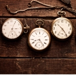 A row of four antique pocket watches on a old wooden table.