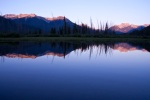 Sunset over Vermilion Lakes in Banff, Alberta with mountain reflections.